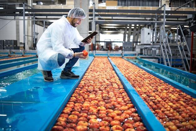 Tecnologo con computer tablet che fa il controllo di qualità della produzione di frutta mela nello stabilimento di trasformazione alimentare.