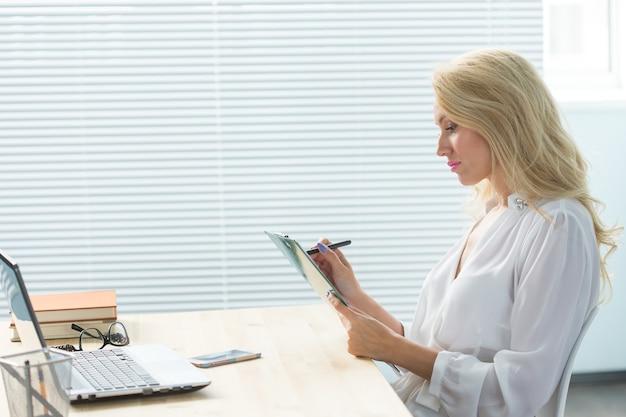 Concetto di tecnologia, affari e persone - bella donna con gli occhiali che lavora al computer e che prende appunti