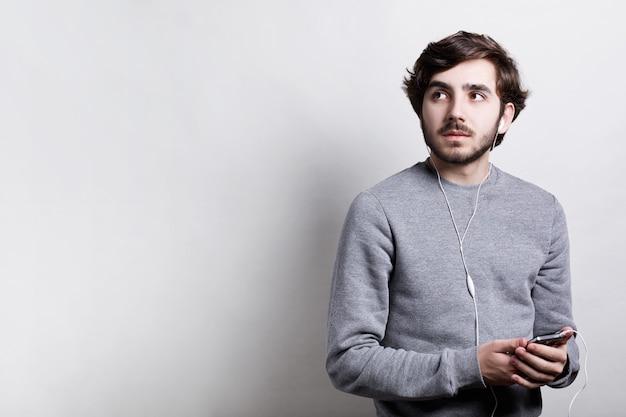 Concetto di tecnologia e comunicazione. giovane uomo alla moda con la barba che porta maglione grigio che ascolta la musica sulle cuffie bianche facendo uso del suo smartphone che cerca da parte isolato sopra la parete bianca
