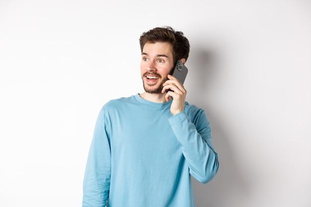 Concetto di tecnologia. uomo allegro che parla sul telefono cellulare, avendo telefonata e guardando divertito, in piedi su sfondo bianco.