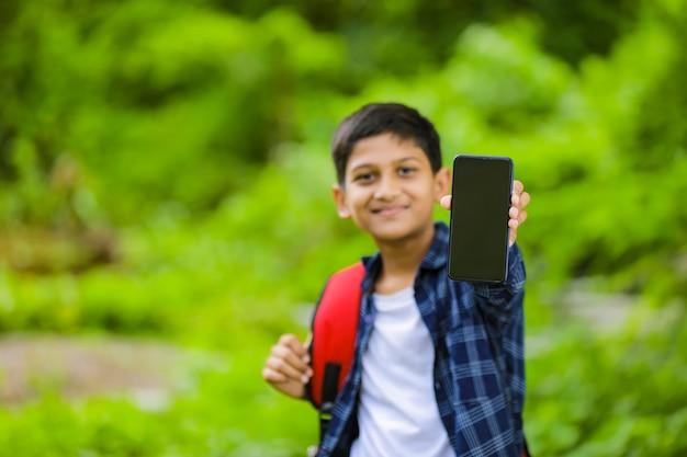 Concetto di tecnologia: sacchetto della holding del ragazzino di scuola indiano carino e mostrando smartphone