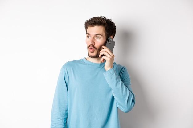 Concetto di tecnologia. giovane incuriosito che guarda lasciato impressionato, parlando al cellulare, chiamando qualcuno, in piedi su sfondo bianco.