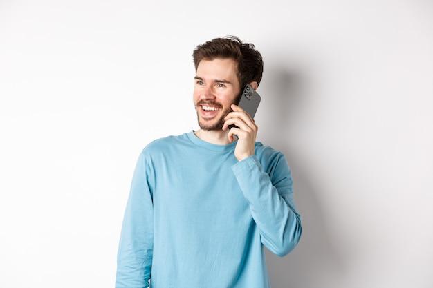 Concetto di tecnologia. uomo gioioso che gode della telefonata, parla sullo smartphone e sorridente, in piedi in camicia casual su sfondo bianco.