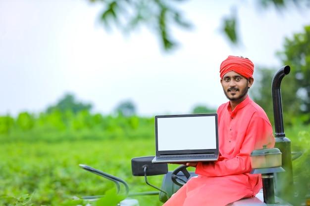 Concetto di tecnologia: giovane agricoltore indiano che mostra lo schermo del laptop