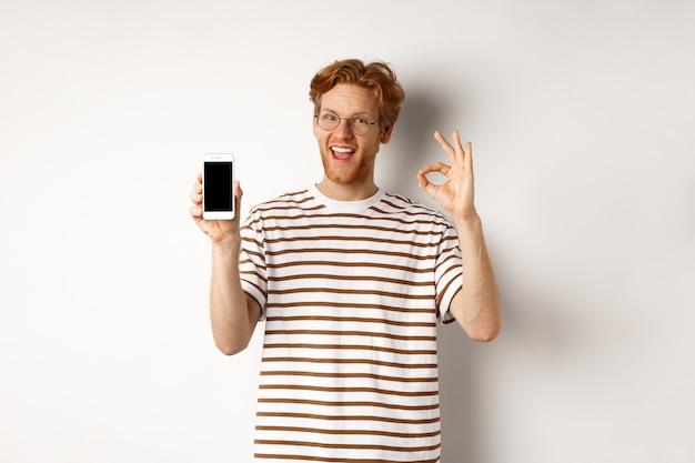 Concetto di tecnologia e e-commerce. giovane con i capelli rossi che mostra il segno giusto e lo schermo vuoto dello smartphone, lodando l'app fantastica, in piedi su sfondo bianco.