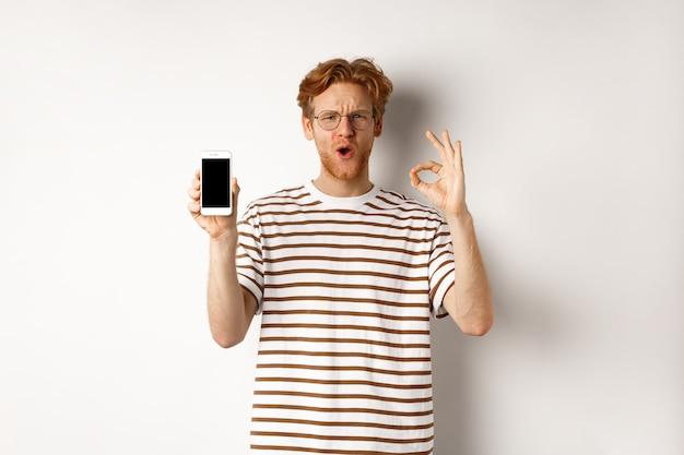 Concetto di tecnologia e e-commerce. giovane con i capelli rossi che mostra il segno giusto e lo schermo in bianco dello smartphone, lodando l'app fantastica o il videogioco, sfondo bianco.