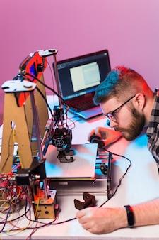 Concetto di tecnologia e ingegneria - ingegnere maschio che lavora di notte in laboratorio, sta regolando i componenti di una stampante 3d.