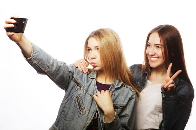 Tecnologia, amicizia e concetto di persone: due adolescenti sorridenti che scattano foto con la fotocamera dello smartphone