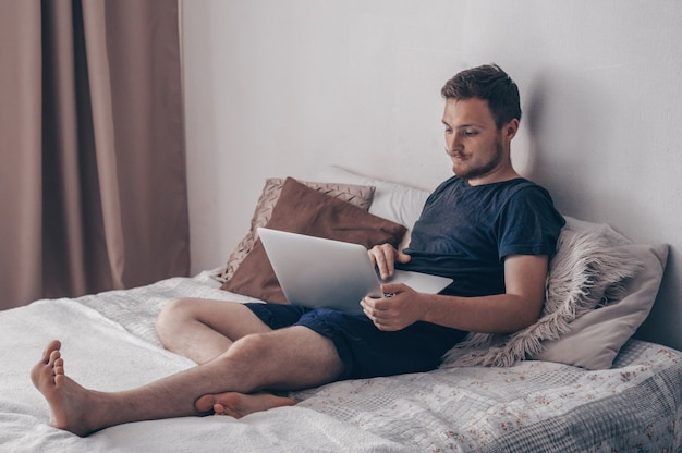 Concetto di tecnologia, casa e stile di vita - chiuda in su dell'uomo che lavora con il computer portatile e seduto sul divano di casa. giovane che utilizza il suo laptop con il sorriso mentre era seduto sul letto di casa