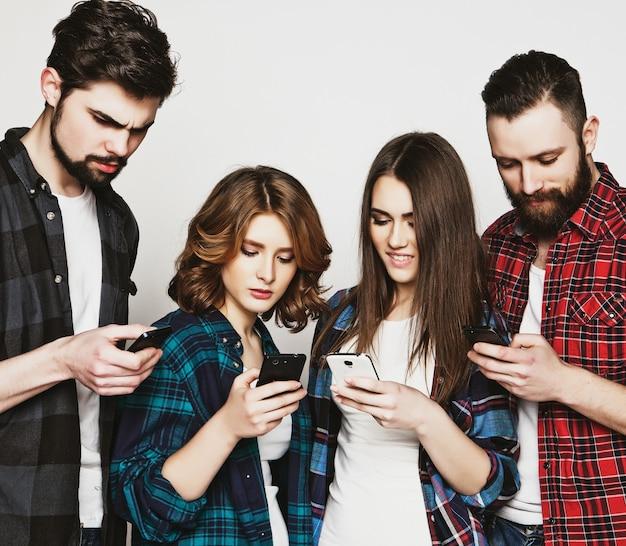 Tecnologia e concetto di internet: un gruppo di giovani che guardano i loro smartphone