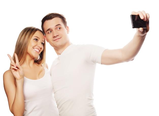 Tecnologia, amore e concetto di amicizia - coppia sorridente con smartphone, selfie e divertimento. studio girato su sfondo bianco.