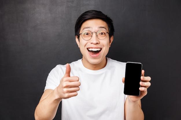 Tecnologia, messaggistica e concetto di persone. ritratto di close-up di eccitato, felice giovane uomo asiatico mostra pollice-up e display del telefono cellulare, sorridendo stupito, vota una buona app, raccomandare l'abbonamento