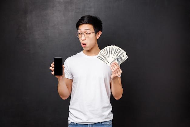 Concetto di tecnologia, denaro e premi. il giovane ragazzo asiatico stupito e sorpreso non riesce ancora a credere di aver vinto soldi tramite omaggi in internet, mostrando il display del cellulare e dollari in contanti