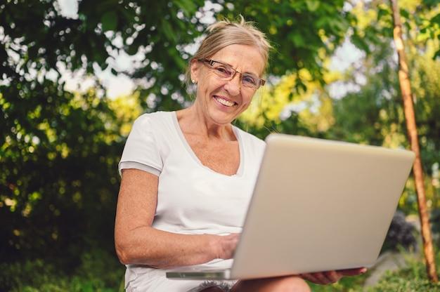 Tecnologia, concetto di persone di vecchiaia - donna anziana senior felice anziana che lavora in linea con il computer portatile all'aperto nel giardino. lavoro a distanza, istruzione a distanza.