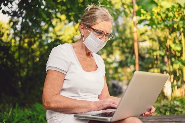 Tecnologia, concetto di persone di vecchiaia - donna anziana senior anziana in maschera protettiva per il viso lavorando in linea con il computer portatile all'aperto nel giardino. lavoro a distanza, istruzione a distanza.