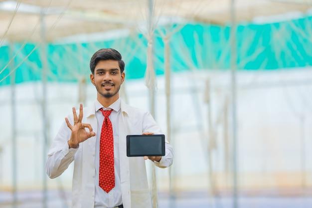 Concetto di tecnologia e persone, giovane agronomo indiano che mostra tablet o smartphone in serra