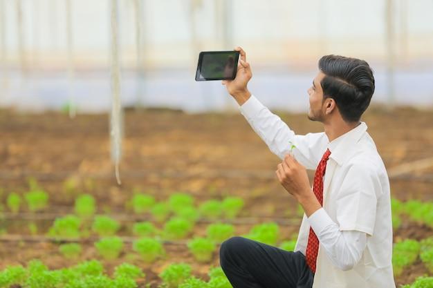 Concetto di tecnologia e persone, giovane agronomo indiano prende selfie in tablet o smartphone in serra