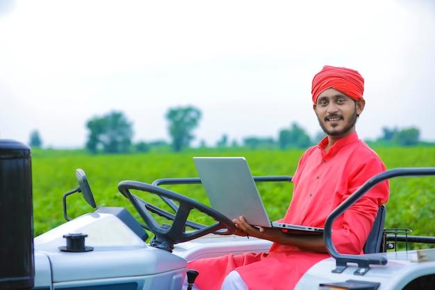Concetto di tecnologia e persone: giovane agricoltore indiano utilizzando laptop al campo