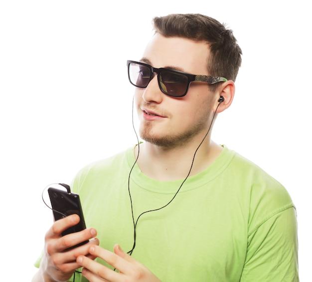 Concetto di tecnologia e persone. giovane uomo che indossa t-shirt verde ascoltando musica e utilizzando smartphone, isolato su bianco