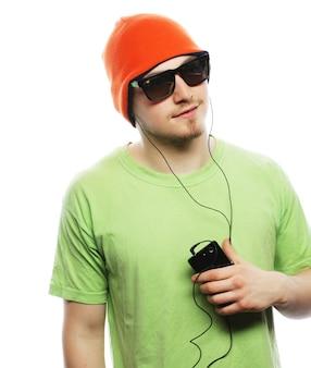 Tecnologia e concetto di persone - giovane che indossa una t-shirt verde che ascolta musica e utilizza smartphone, isolato su bianco