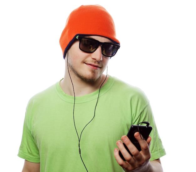 Tecnologia e concetto di persone - giovane che indossa una maglietta verde che ascolta musica e usa smartphone, isolato su bianco,