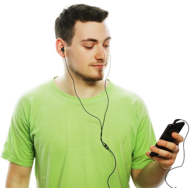 Tecnologia e concetto di persone - giovane che indossa una t-shirt verde che ascolta musica e usa lo smartphone, isolato su bianco