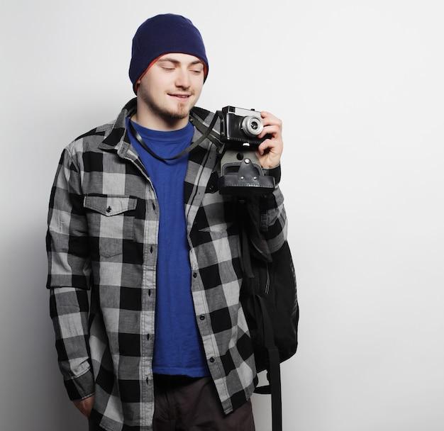 Tecnologia, persone e concetto di stile di vita: giovane fotografo su sfondo bianco