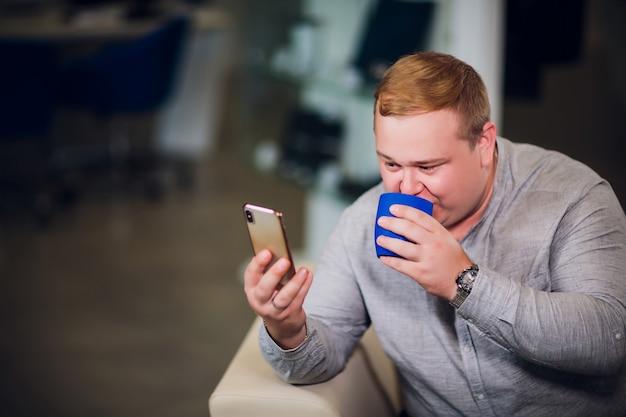 Concetto di tecnologia, della gente, di stile di vita e di comunicazione - uomo felice con il telefono che ha casa di video chiamata e che mostra i pollici su che si siedono sul sofà in ufficio