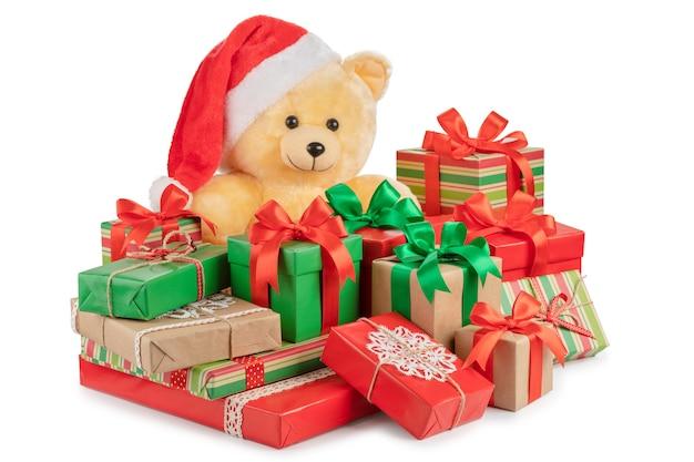 Orsacchiotto e scatole con doni isolati su bianco.