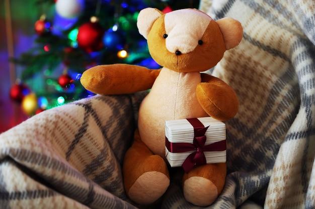 Orsacchiotto e confezione regalo sulla sedia a dondolo sull'albero di natale