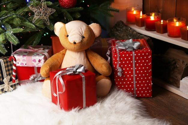 Orsacchiotto e scatole regalo vicino all'albero di natale, primo piano