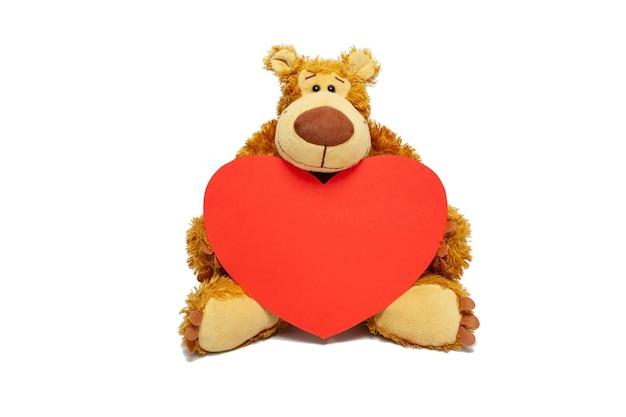 Orsacchiotto di peluche che tiene un cuore di cartone, per il giorno di san valentino. vista frontale, copia dello spazio.