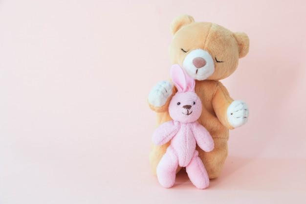 Un orsacchiotto abbraccia il coniglio con uno sfondo rosa
