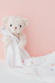 Orsacchiotto è abbracciare asciugamano con sfondo pastello rosa, carino orsacchiotto coperto asciugamano dopo il bagno