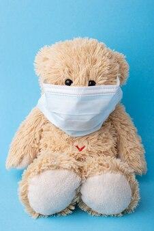 Orsacchiotto di peluche in una mascherina medica su sfondo blu