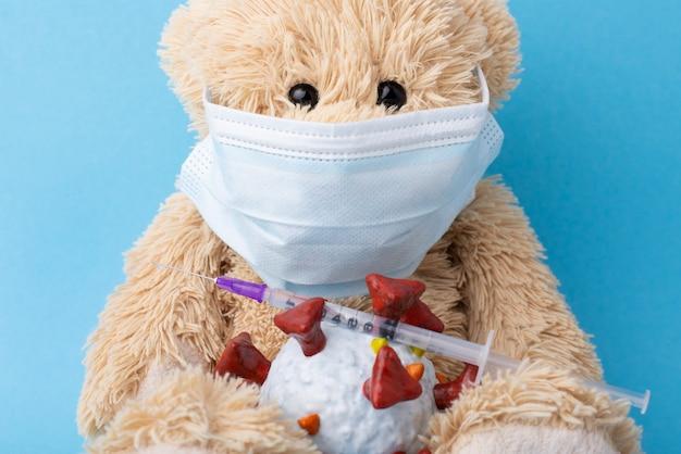 Orsacchiotto in maschera medica con giocattolo modello covid-19 e siringa con vaccino