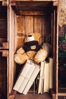 L'orsacchiotto si siede sui libri in una scatola di legno sulla parete.