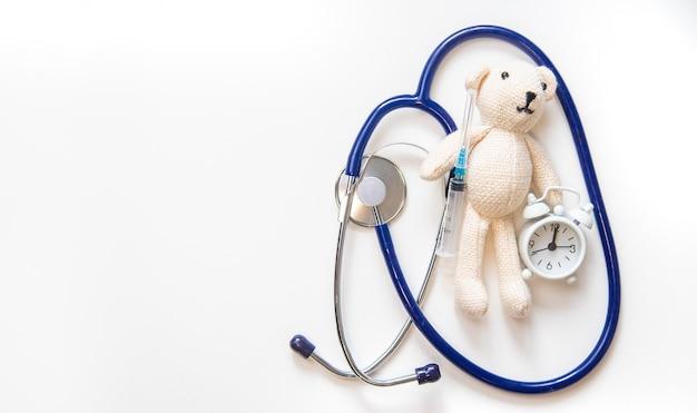 Lo stetoscopio e la siringa dell'orsacchiotto isolano su un fondo bianco. messa a fuoco selettiva.