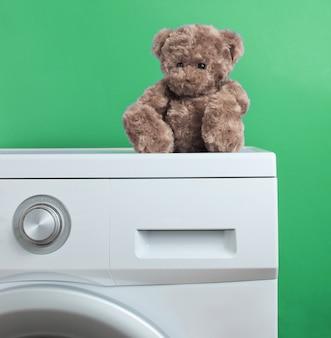 Orsacchiotto di peluche su una lavatrice su sfondo verde