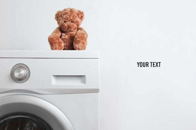 Orsacchiotto di peluche su una lavatrice contro uno sfondo bianco con copia spazio