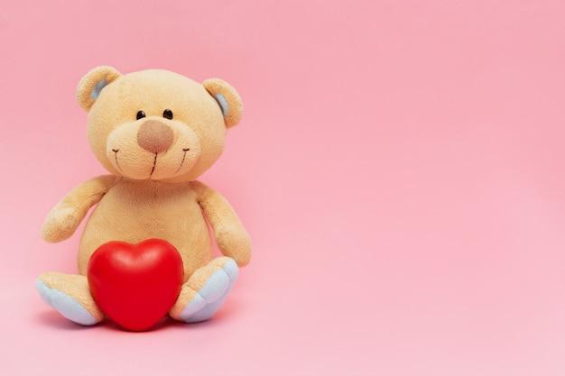 Orsacchiotto con grande cuore rosso isolato su sfondo rosa concetto di giorno di san valentino con spazio di copia.
