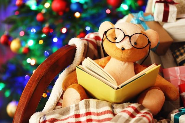 Orsetto con libro e scatole regalo su sedia a dondolo
