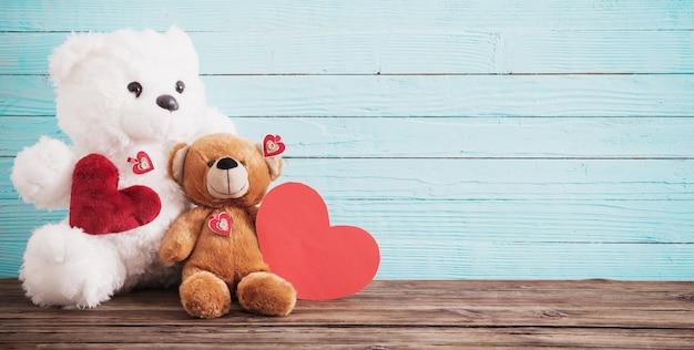 Orsacchiotto di peluche con cuore rosso su sfondo di legno vecchio. concetto di san valentino