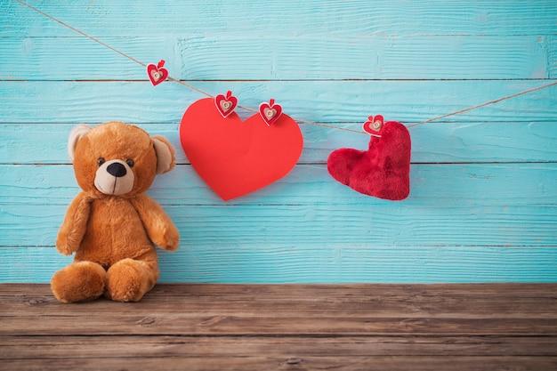 Orsacchiotto con cuore rosso su fondo in legno vecchio. san valentino