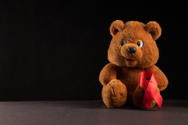 Orsacchiotto con nastro rosso hiv, aids su sfondo scuro, consapevolezza, segno medico. copia spazio.
