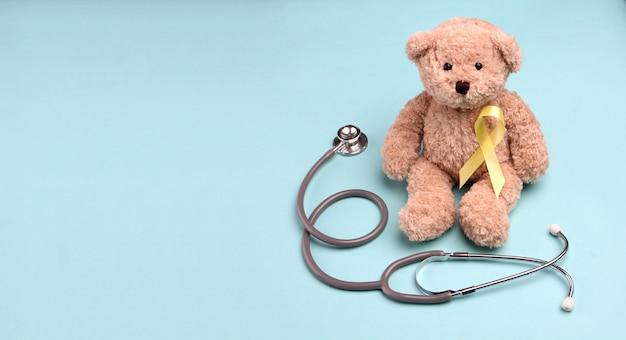 Nastro in oro giallo orsacchiotto con stetoscopio su sfondo blu.