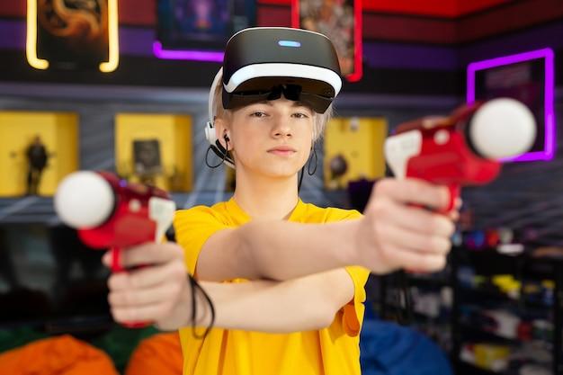 Adolescente, bambino che gioca su una console per videogiochi, giocatore emotivo che spara a un gioco usando un controller di pistola in un club di gioco. vr