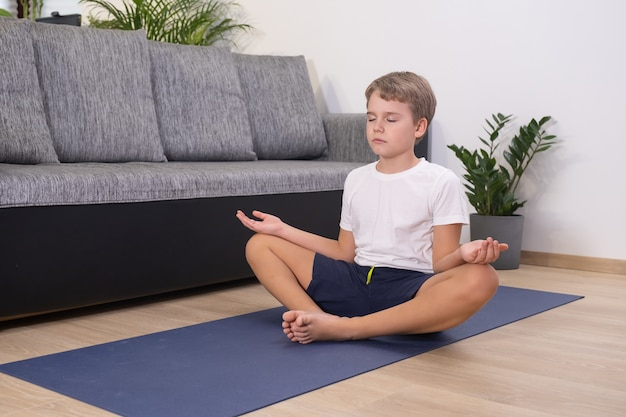 Ragazzo biondo adolescente che esercita sport a casa pratica yoga sedersi in posa mantenere la calma meditando attività fisica del bambino stile di vita sano