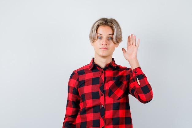 Teen bionda maschio agitando la mano per il saluto in camicia casual e guardando pensieroso, vista frontale.