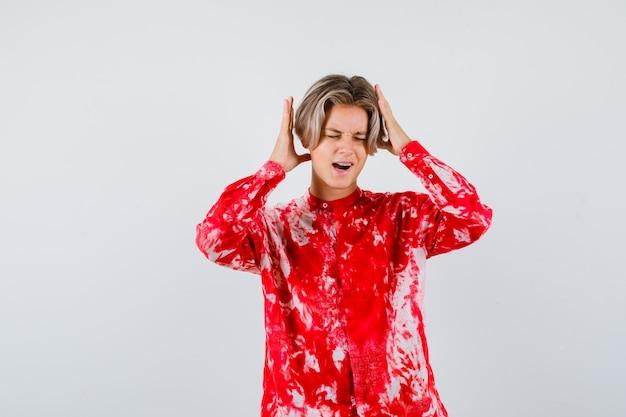 Maschio biondo teenager con le mani vicino alla testa in camicia surdimensionata e sembra turbato. vista frontale.